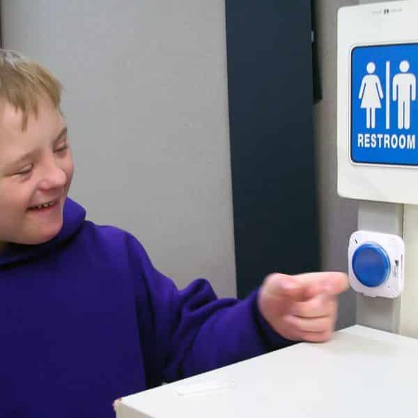 Pojke som trycker på en TalkingBrix talknapp utanför en toalett.