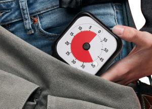 Ung person håller Time Timer Pocket i handen och har precis tagit upp den ur sin axelremsväska.